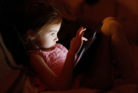 Little girl playing on a tablet